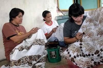 pekerja batik sedang melakukan proses canting